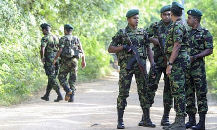Security personnel patrol outside a polling station in Weerawila, Sri Lanka