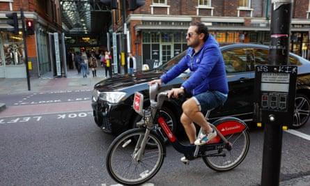 Cyclist riding hire bike alongside BMW car in Shoreditch, London