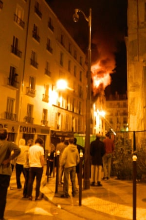 People stand in the street below as flames and smoke billow out of the window of an apartment building in the north of Paris.
