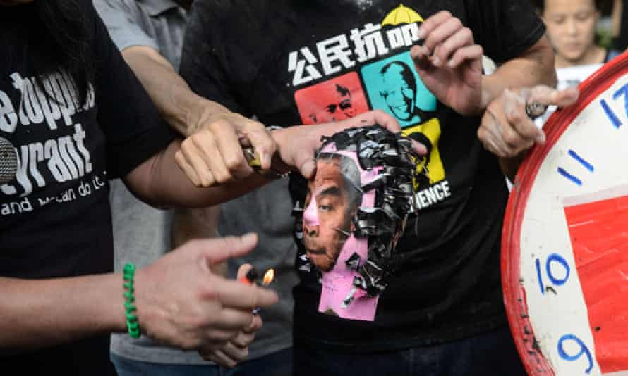 Activists set fire to a paper model of Hong Kong chief executive CY Leung.