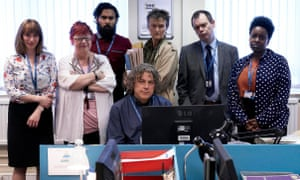The cast of Dammed, including Jo Brand, standing around Alan Davies, sitting at a computer.