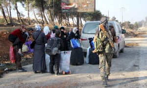 Displaced Syrians carry their belongings out of Aleppo on the third day of a rebel offensive.