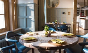 The Restaurant at The Painswick. Shown is a round wooden table with linen napkins and cork place mats; light streams in from a nearby window.