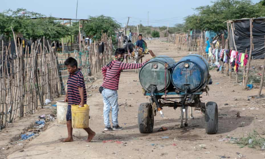 Two boys deliver water to a shack in La Pista.Water costs 3,000 pesos (about 5560p) a day for those who can afford it.