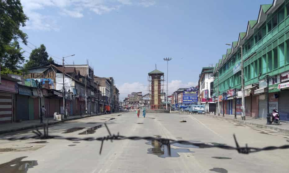 Kashmiri women walk at a deserted Lal Chowk square.