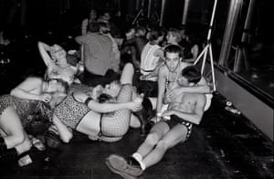a black and white photograph of revellers lying on the gound