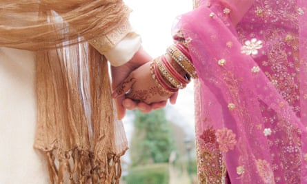 A couple in traditional Muslim wedding attire from India holding hands