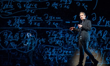 brian greene giving a lecture strolling on a big stage backlit with equations