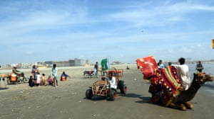 People visit the beach after the government lifted most of the country's remaining coronavirus restrictions, in Karachi.