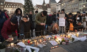 People light candles at the Christmas market where the previous day Cherif Cherkatt opened fire.