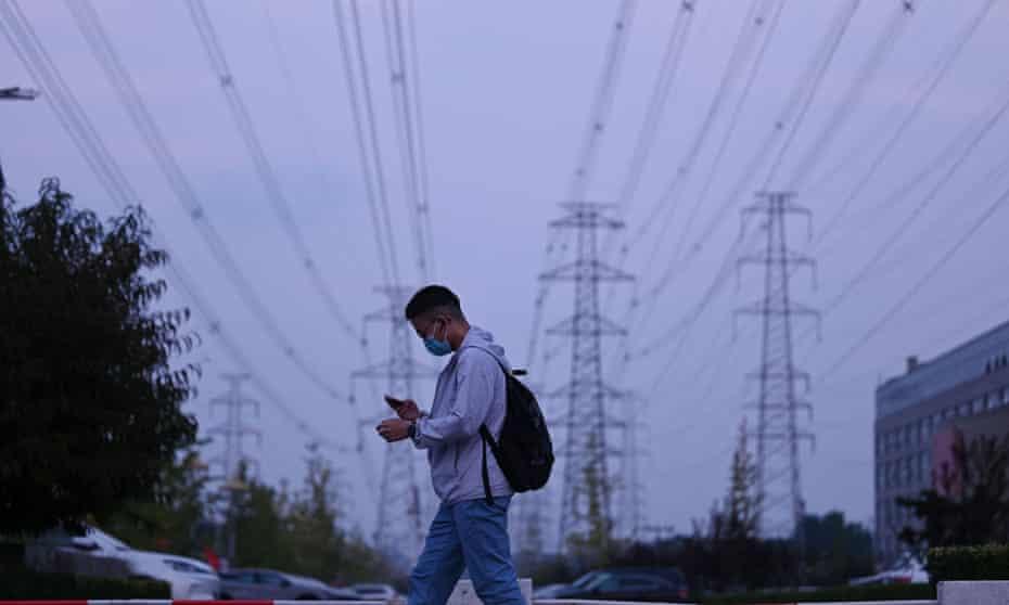 A man walks below power lines in Beijing on 28 September