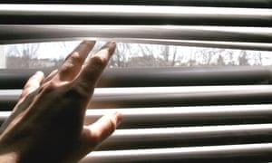 Someone peeks through a blind
