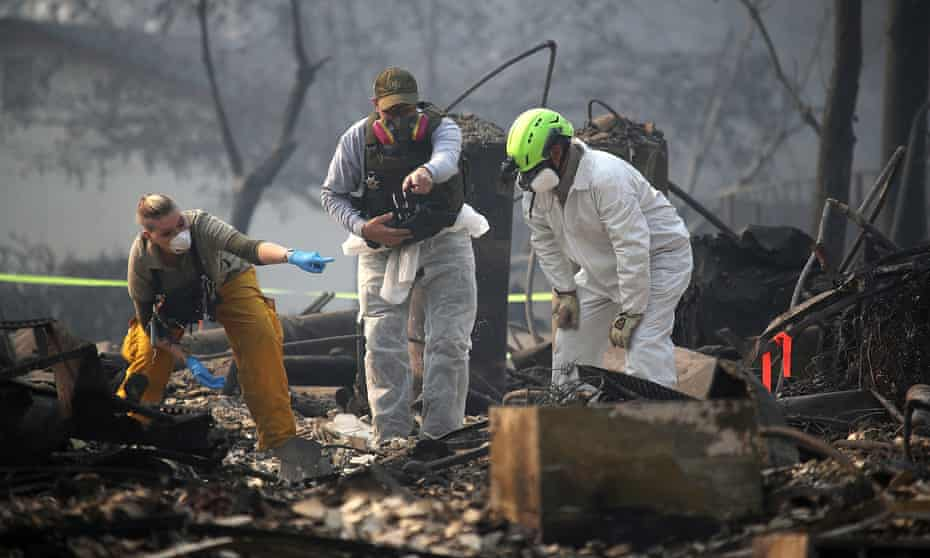 Rescue workers search an area where they discovered suspected human remians in a home destroyed by the Camp Fire on Friday in Paradise, California.