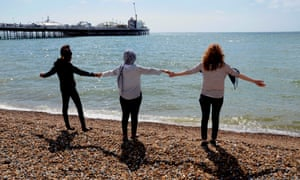 Mariam, centre, with two more young asylum seekers on Brighton beach.