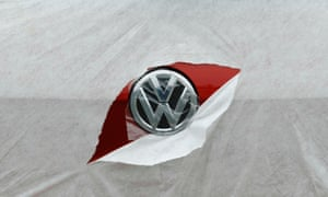 A VW badge is seen through torn wrapping as a Volkswagen Golf is delivered to a car dealership in Portslade near Brighton.