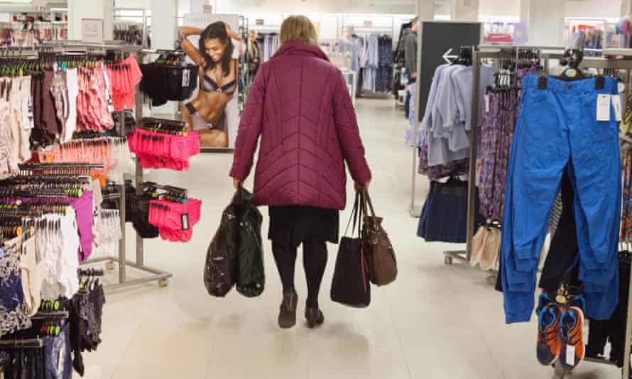 A woman walks through an M&S clothing department