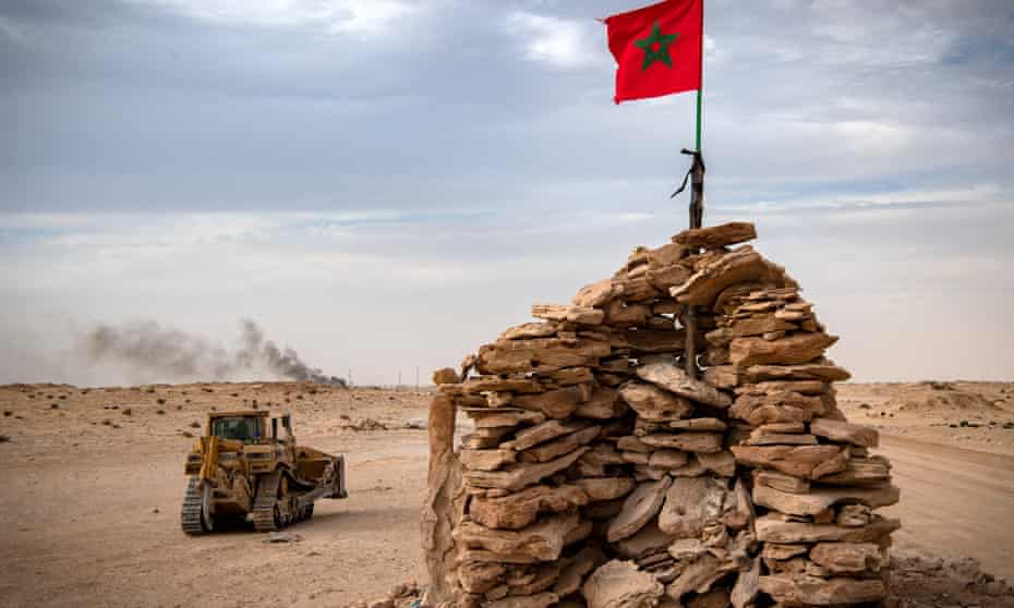 A bulldozer passes by a hilltop manned by Moroccan soldiers in Guerguerat in the Western Sahara in November 2020