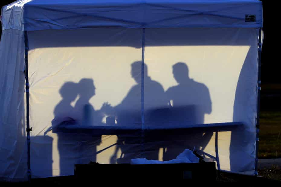 Medical personnel are silhouetted against the back of a tent at a coronavirus test site in Tampa, Florida.