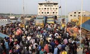 Migrant people and workers walk to board a ferry as they leave the city before the countywide lockdown imposed as cases increased, at Mawa ferry port in Munshiganj, Bangladesh.