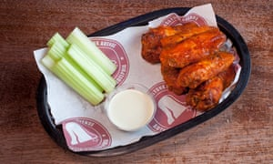 A pile of sticky red buffalo chicken wings with sticks of celery and a white dip, in a basket