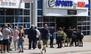 Shoppers queue outside Sports Direct in Brighton.