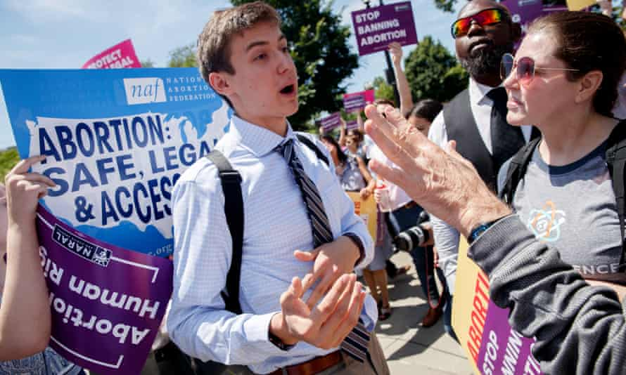 An anti-abortion protester debates with pro-abortion rights activists at the supreme court.