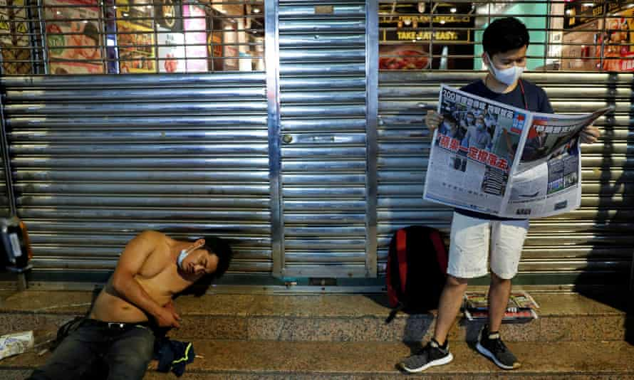 A supporter of Apple Daily newspaper reads a copy.