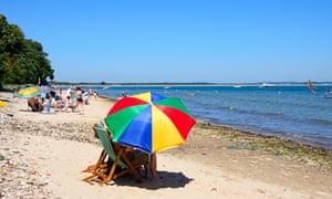 Holidaymakers relaxing on the beach in Studland Bay, Dorset.