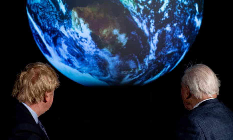 Boris Johnson (left) and British broadcaster and naturalist Sir David Attenborough look at a projection of planet Earth during the launch of the COP26 UN Climate Summit.