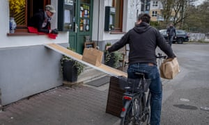A man on a bike picks up food to go in front of a famous apple cider restaurant, 'Zum Lahmen Esel,' in Frankfurt, Germany, Friday, April 3, 2020.