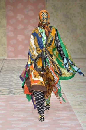 A model dressed completely in different coloured head scarves, including one covering her face