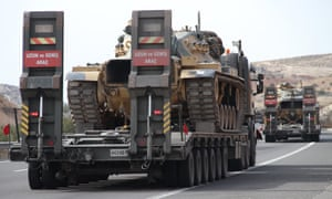 Turkish military trucks carry armoured vehicles towards the Syrian border near Gaziantep on Tuesday.