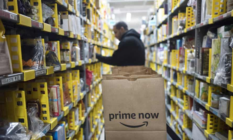 A worker picks an item for a customer order at the Amazon Prime warehouse, in New York