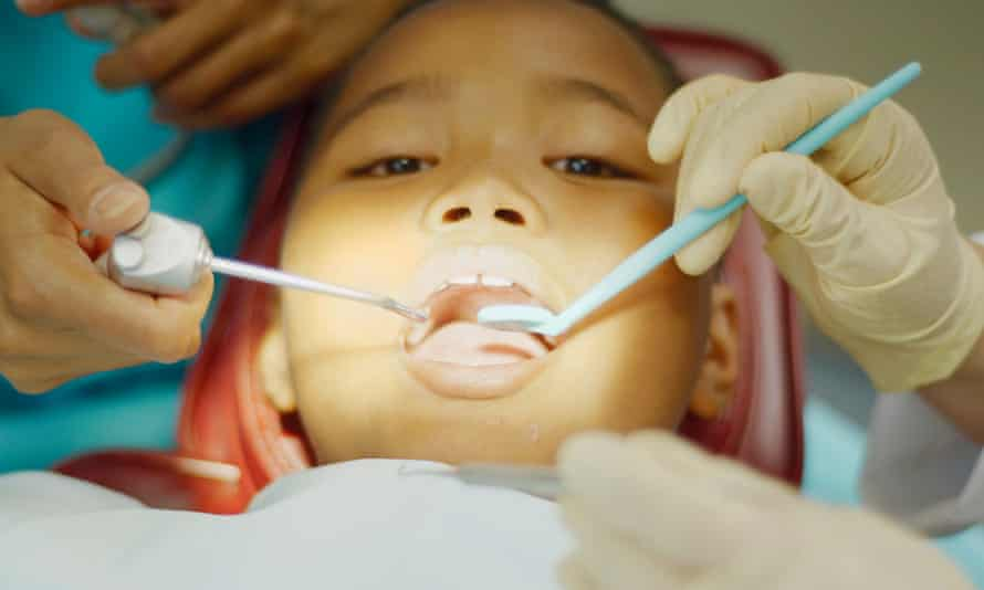 Young boy being examined by dentist