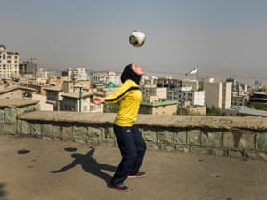 Katayoun Khosrowyar in a hijab, yellow football shirt, track suit bottoms and trainers, heading a ball in an open space with the city of Tehran behind