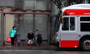 People wear masks as they wait or a San Francisco MUNI bus during the coronavirus pandemic on 6 April 2020 in San Francisco, California.