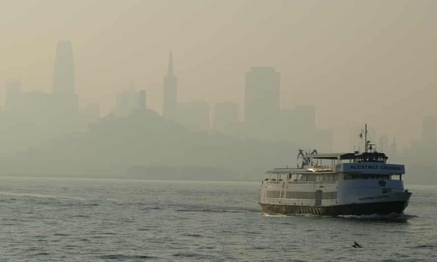 A ferry boat makes its way through the haze toward Alcatraz Island.
