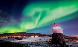 Aurora borealis or northern lights are visible in the sky above a lighthouse to the village of Strand, Norway.