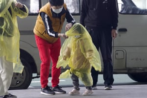 A woman puts a poncho on a child at Wuhan Tianhe international airport
