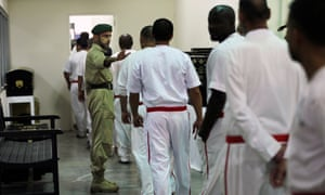 A policeman directs prisoners at Central Prison in Dubai, United Arab Emirates.