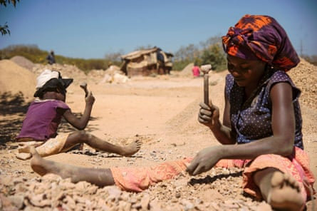 A child and a woman break rocks extracted from a cobalt mine in Lubumbashi, Democratic Republic of the Congo