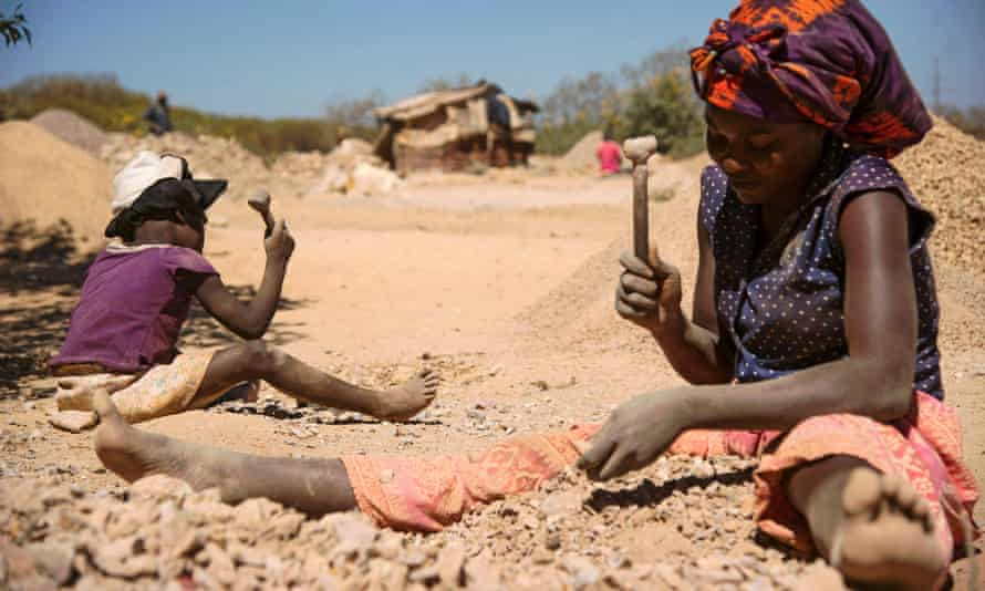 A child and a woman break rocks at a copper quarry and cobalt pit in Lubumbashi, DRC.