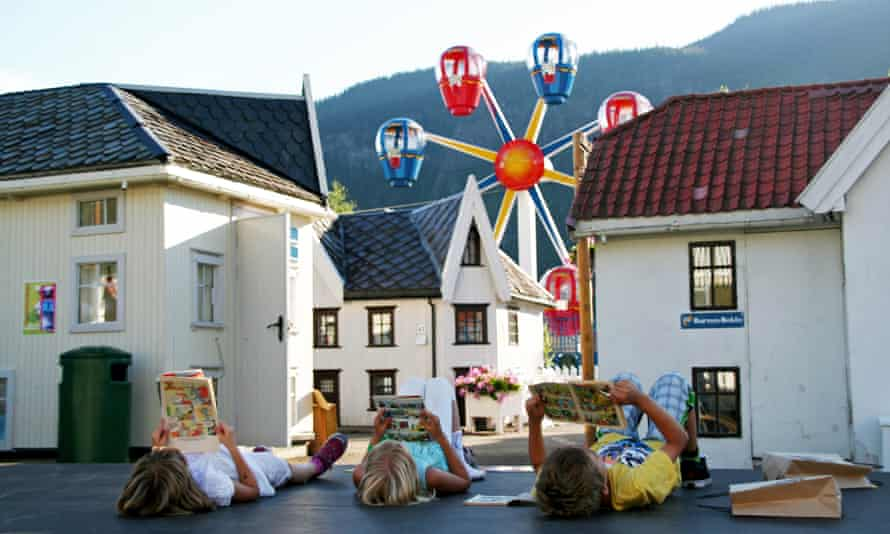 Children lie on their backs reading comics amid the quarter-size houses of the adventure park in Lilleputthamer, Norway.