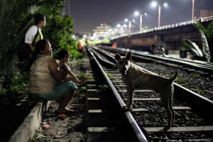 A mother (L) and child sitting along a train track in Manila, waiting for trolley boys