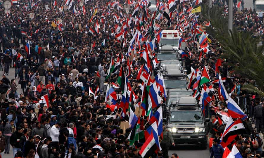 Pro-Assad supporters wave Syrian and Russian flags as they cheer a convoy believed to be transporting Russian diplomats in Damascus, Syria, in 2012.