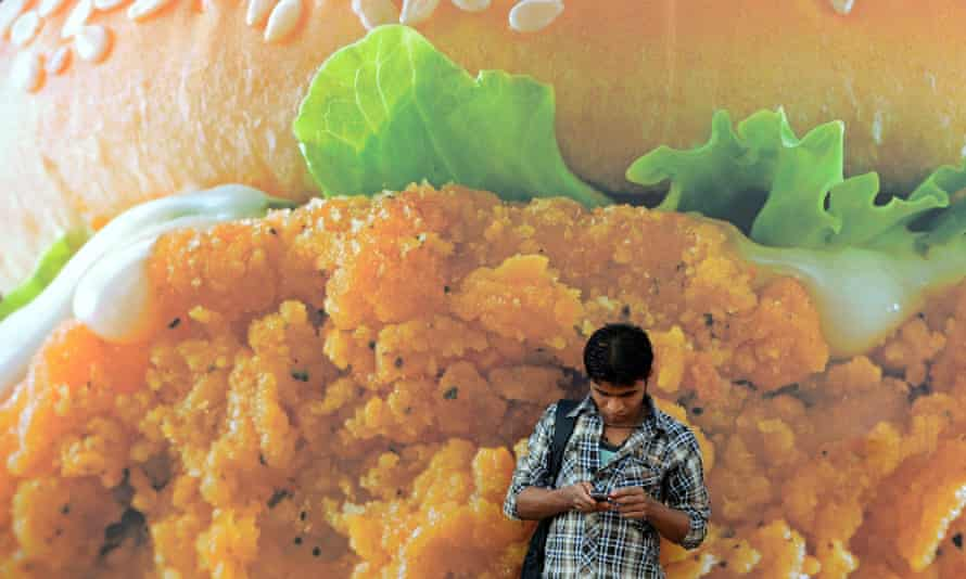 An Indian pedestrian checks his mobile phone in front of an advertisement for a burger of a fast food giant in Mumbai on February 20, 2013