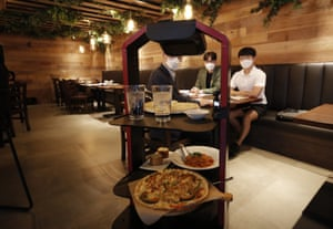 A robot serves food and drink during a demonstration at a restaurant in Seoul, South Korea