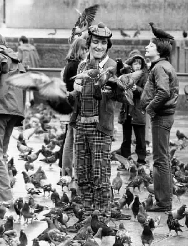 Clad in tartan, a Scottish football supporter feeds the pigeons in Trafalgar Square, London.