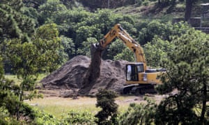 Forensic science experts use an excavator to dig in an old well turned into a mass grave where, up to now, 75 bags with human remains have been found, in the community La Primavera in Zapopan, near Guadalajara in Mexico.