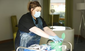 Megan Watt, a senior social care worker dons PPE at the David Walker Gardens care home in South Lanarkshire.